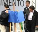 Lula faz graça se escondendo atrás do pano que cobre a placa de inauguração